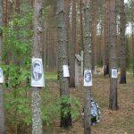 Портрети українців, розстріляних в Сандармоху. На задньому плані — одна з ям, позначена традиційними в Карелії хрестами з дашками